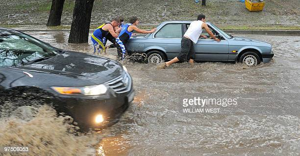 Passerbys help push a car down a flooded road in central Melbourne after a severe storm passed through the city causing the cancellation of major...