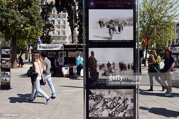Passers by look at an open air photo exhibition commemorating the centenary of the massacre of some 15 million Armenians by Ottoman forces in Athens...