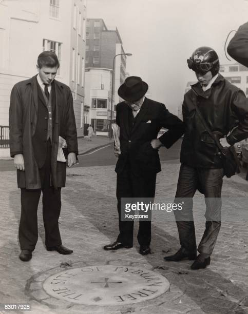 Passers by looking at the plaque on the site of Tyburn Tree gallows at the junction of Edgware Road and Bayswater Road in London, circa 1964.
