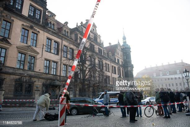 Passersby and journalists stand in front of the cordoned off Royal Palace that houses the historic Green Vault in Dresden eastern Germany on November...
