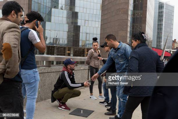 Passersby are entertained by the three cup scam on London Bridge on 30th May 2018 in London England