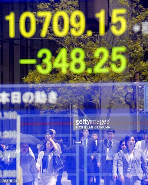 Passersby are reflected on a stock indicator at the window of a securities company in Tokyo on May 6 2010 The headline Nikkei index at the Tokyo...