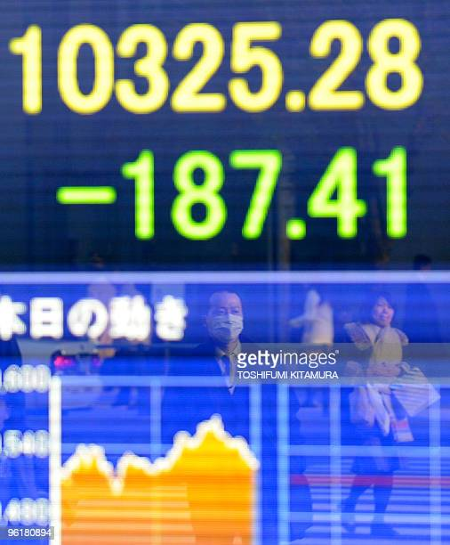 Passersby are reflected on the electric stock indicator flashing the Tokyo Stock Exchange's closing rate at the window of a securities company in...