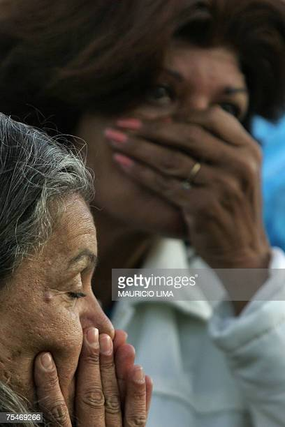 Passersby cover their nostrils to avoid the stench as they look at rescuers working on a colapsed building and on the charred wreckage of the Tam...