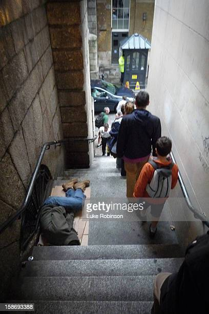Passers-by ignore a homeless man curled on piece of cardboard in a set of stairs leading down from London Bridge.