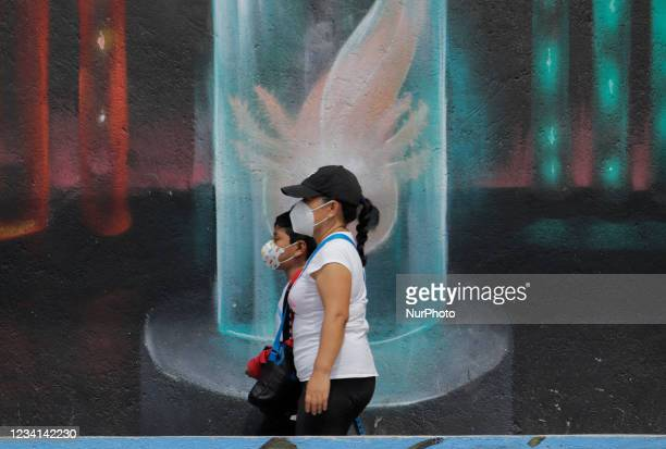 Passers-by in front of a mural of an axolotl in the esplanade of the Plaza Cívica Quirino Mendoza in Santiago Tulyehualco in Mexico City, Mexico, on...