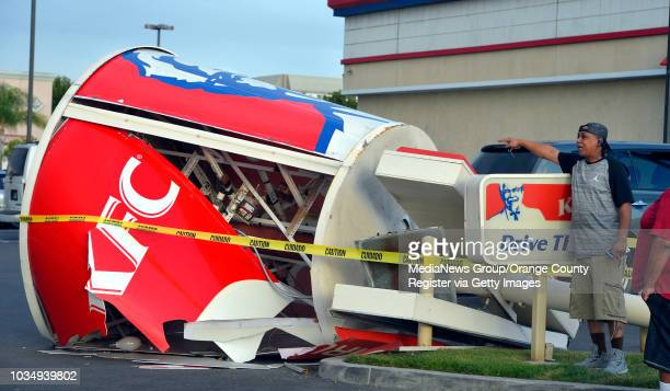 Passersby inspect a downed sign after strong winds toppled the giant chicken bucket sign at the KFC in the 4500 block of Atlantic Avenure in Long...