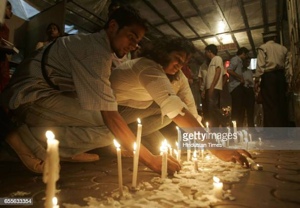 Passersby lit candles offering tribute to 26/11 terror attack victims outside Leopold Cafe