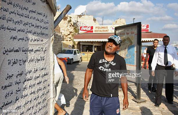 Passersby look at a monument erected in memory of Issa alAwam who fought alongside warrior Salaheddine alAyyubi in 1189 AD in the Arab Israeli port...