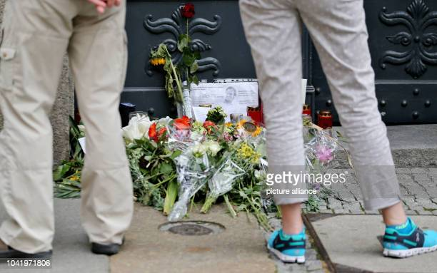 Passersby look at flowers and memorial candles outside the entrance to the Unister company headquarters in Leipzig Germany 18 July 2016 The Leipziger...