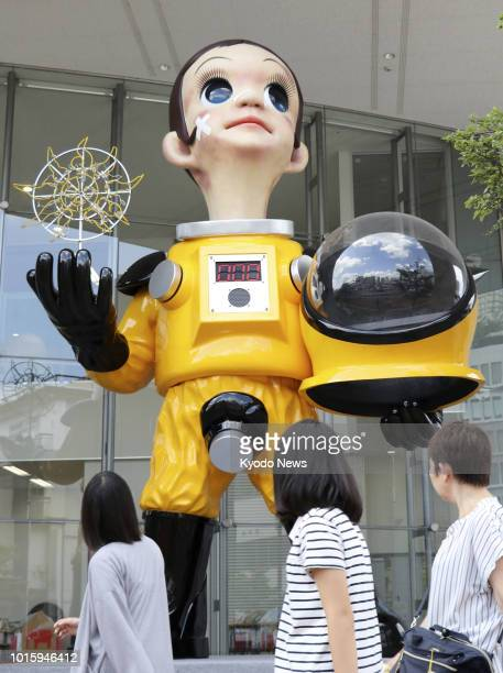 Passersby look at Sun Child a 62meter statue clad in a protective suit near JR Fukushima Station in northeastern Japan on Aug 12 2018 The statue...
