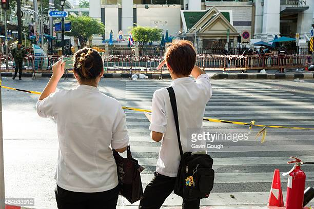 Passers-by look at the scene of the explosion on August 18, 2015 in Bangkok, Thailand. Workers clean up debris from the site of the explosion on...