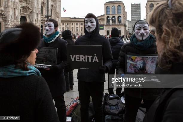 Passersby look on as members of Anonymous for the Voiceless wearing Guy Fawkes mask perform 'The Cube of Truth' a static protest which consists in...
