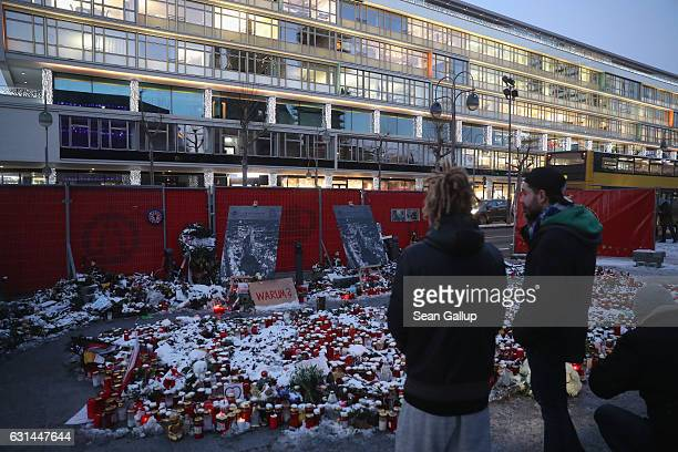 Passersby pause at a memorial to the December 19 terror attack at Breitscheidplatz on January 10 2017 in Berlin Germany The Bundestag has announced...