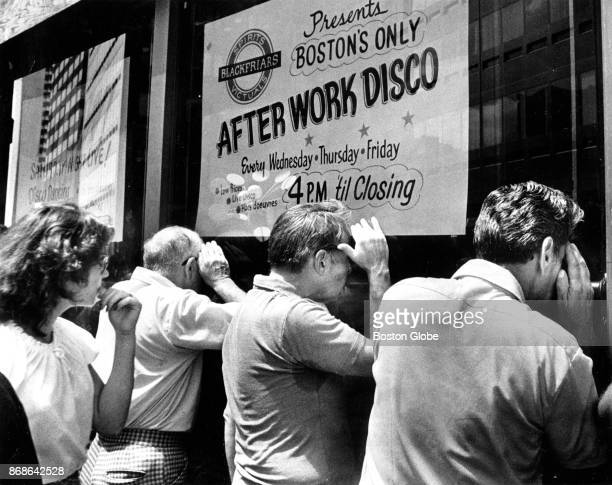Passersby peer into the Blackfriars lounge at 105 Summer St in Boston where the bodies of five men were found in the basement office on Jun 28 1978...