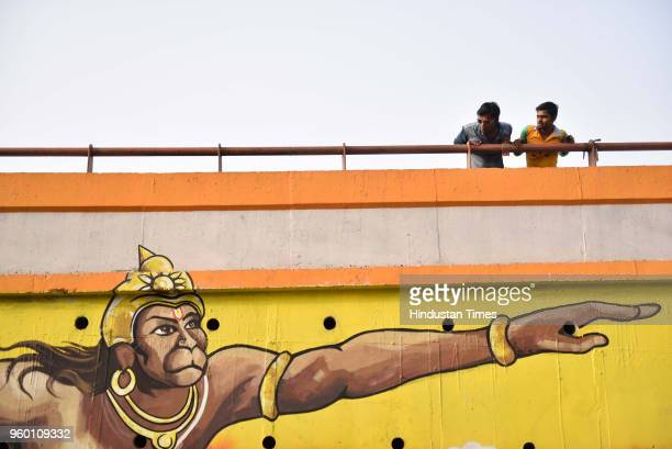 Passersby peer over the flyover across the Old Hanuman Mandir at Yamuna Bazar near Kashmere Gate on May 16 2018 in New Delhi India Arm outstretched...