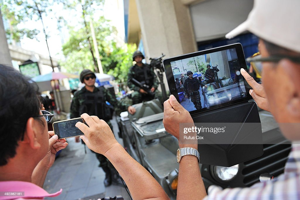 Passersby photo Thai army soldiers standing guard on a city centre street after martial law was declared on May 20, 2014 in Bangkok, Thailand. The army imposed martial law across Thailand amid a deepening political crisis that has seen six months of protests and claimed at least 28 lives.