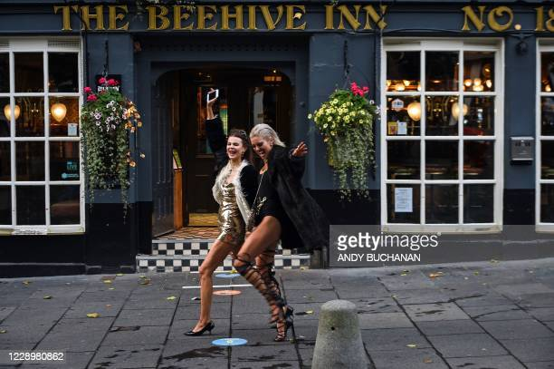 Passers-by pose for a photograph as they pass The Beehive Inn as the time nears 1800 BST in Edinburgh on October 9 as new restrictions come into...