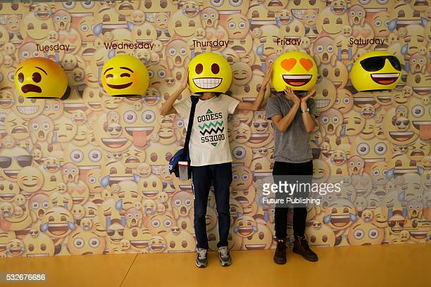 Passersby pose for photos with emoji hats fixed on a wall in a shopping mall in Guangzhou on May 18 2016 in Guangdong China Feature China / Barcroft...