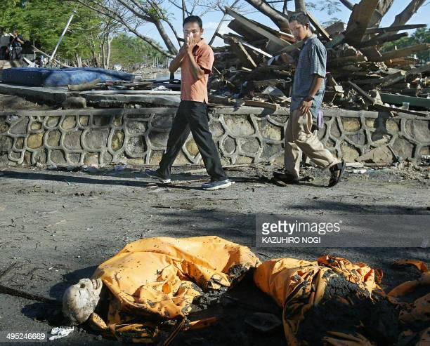 Passersby react to a dead body which has nearly turned into a skeleton at a roadside in downtown Banda Aceh 11 Janaury 2005 The death toll from the...