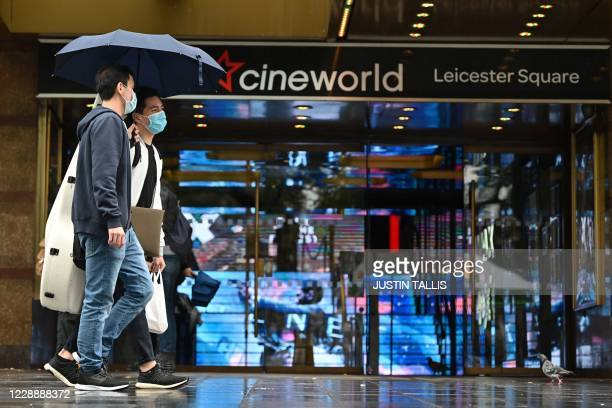 Passersby shelter from the rain under an umbrella walk past a cineworld cinema in Leicester Square in central London on October 4 2020 Cineworld is...