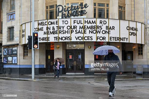 Passersby shelter under umbrellas outside a Picturehouse cinema in west London on October 4 2020 Cineworld which own the Picturehouse chain of...