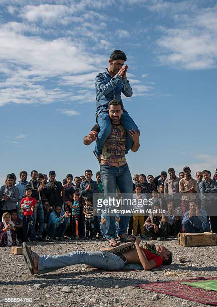 Passersby standing on the belly of a man lying on nail bed during a show on a market hormozgan minab Iran on December 31 2015 in Minab Iran