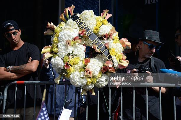 Passersby stop to look at a flowers letters and other momentos at a memorial to Robin Williams at Williams' star on the Hollywood Walk of Fame August...