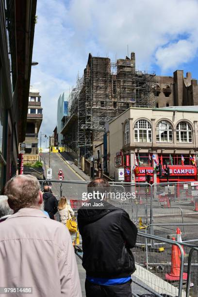 Passersby stop to look at the remains of the Glasgow School of Art Mackintosh building which was completely burned out in a major fire still carry...