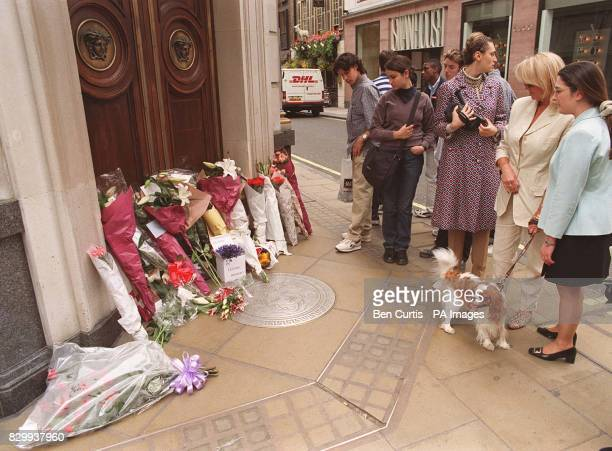 Passersby stop to observe floral tributes outside the London headquarters of murdered fashion designer Gianni Versace today The Italian fashion guru...