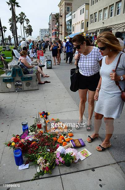 Passersby stop to view a memorial to 32yearold Italian newlywed Alice Gruppioni on the Venice Beach boardwalk on August 4 2013 One day earlier...