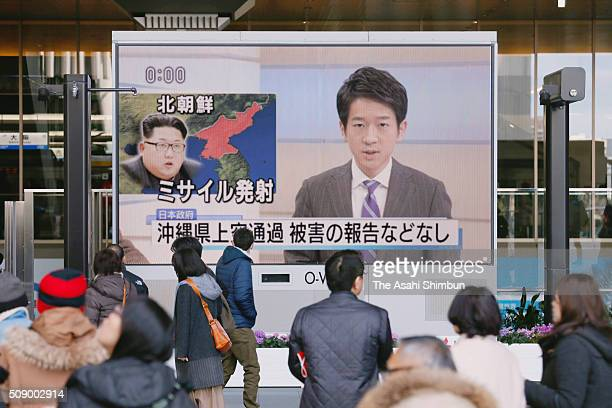 Passersby stop to watch the NHK news on screen following North Korea's rocket launch at the Osaka station on February 7 2016 in Osaka Japan North...