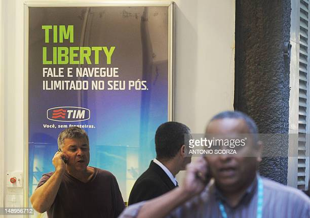 Passersby talk by mobile in front of a Tim mobile phone company store on July 20 2012 in Rio de Janeiro Brazil Three mobile phone companies Claro Tim...