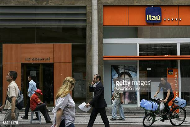 Passersby walk in front of two different agencies of Itau bank at the financial centre in downtown Sao Paulo Brazil on November 3 2008 Brazil's Itau...