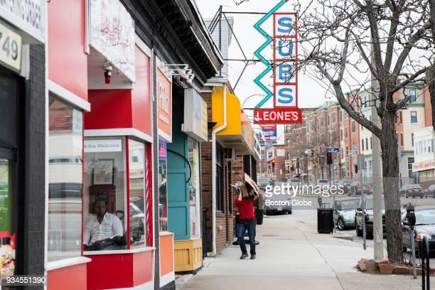 Passersby walk near shops on Broadway in the Winter Hill neighborhood of Somerville MA on March 6 2018