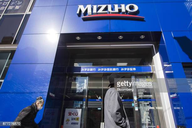 Passersby walk past a Mizuho Bank Ltd branch in the Shibuya district of Tokyo Japan on Thursday Nov 16 2017 Japans economy grew for a seventh...