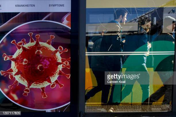 Passers-by walk past an advertising banner for a magazine depicting the coronavirus following the closure of public venues due to the coronavirus on...