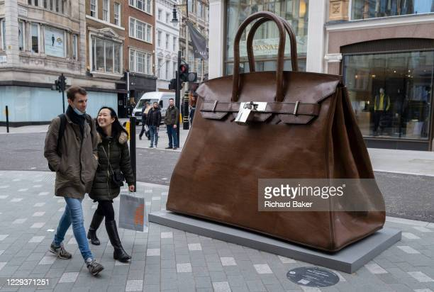 Passersby walk past the oversized artwork of a hand bag accessory entitled 'Bag of Aspirations' by the Greek artist Kalliopi Lemos located on New...