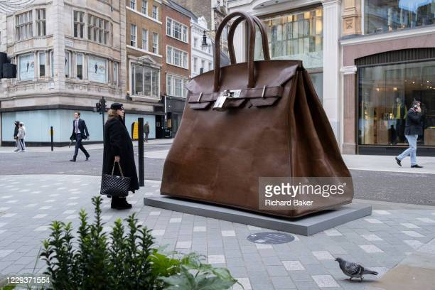Passers-by walk past the oversized artwork of a hand bag accessory entitled 'Bag of Aspirations' by the Greek artist Kalliopi Lemos located on New...