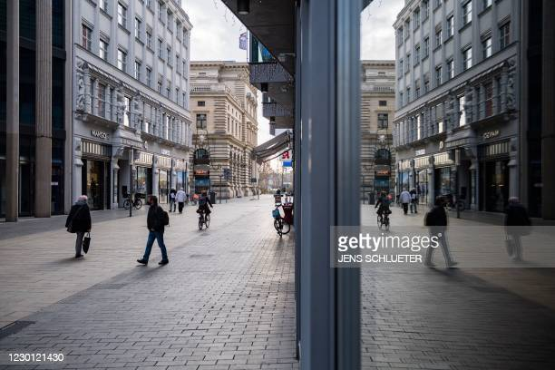 Passers-by walk through the almost deserted shopping streets in the city center in Leipzig, eastern Germany on December 14, 2020 amidst the ongoing...