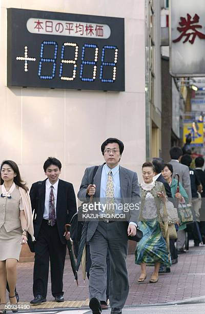 Passersby walk under an electronic indicator showing the closing numbers of the Tokyo Stock Exchange Nikkei225 index in downtown Tokyo 07 June 2004...
