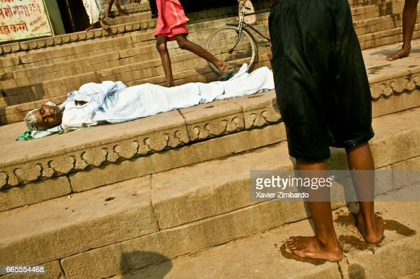 Passersby walking near a corpse looking like a man sleeping on the stairs of a ghat on the banks of River Ganges the most sacred river of Hindus on...