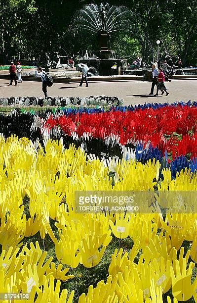Passersby wander past the 'Sea of Hands' symbolising reconciliation between Aborigines and white Australians in Sydney's Hyde Park 26 November 2004...
