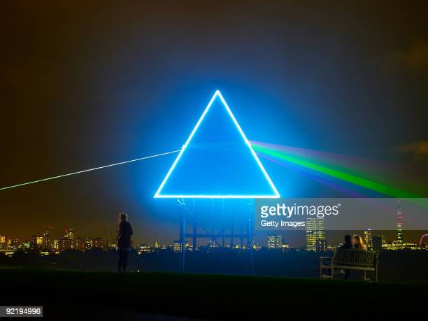 Passersby watch as Sky Arts pays tribute to Pink Floyd's iconic Dark Side Of The Moon album cover on Primrose Hill October 21 2009 in London For one...