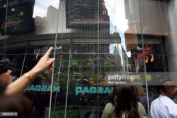 Passersby watch as the stock numbers are posted at the close of the market on the Nasdaq building in Times Square September 29 2008 in New York City...
