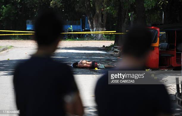 Passers-by watch the corpse of a murdered man in the town of Quezalteque, 25 km west of San Salvador, on July 5, 2013. The victim, 19-year-old Carlos...
