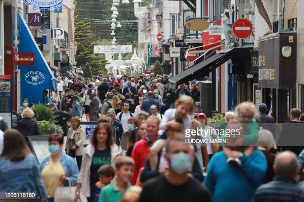 Passers-by, with and without masks, walk in the main street of Le Touquet, western France, on June 27, 2020.