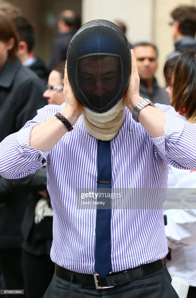 A passing business man tries on a fencing mask during an outdoor fencing demonstration on Sparks Street during the Medley on the Street event on April 20, 2017 in Ottawa, Canada. The Medley on the Street event promotes Fencing Week in Canada and the upcoming National Canadian Fencing Championships.