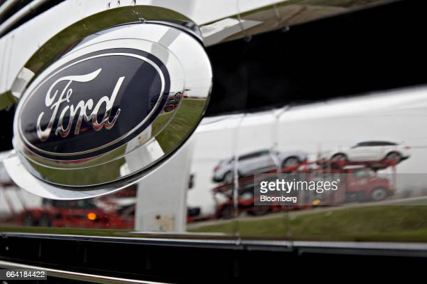 A passing car carrier is reflected in the grille of a 2017 Ford Motor Co F150 pickup truck on display at the Sutton Ford Lincoln car dealership in...