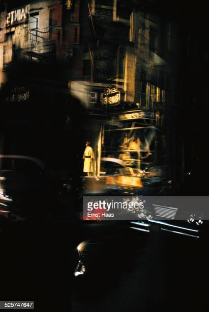 Passing cars and a shop mannequin reflected in a window New York August 1962